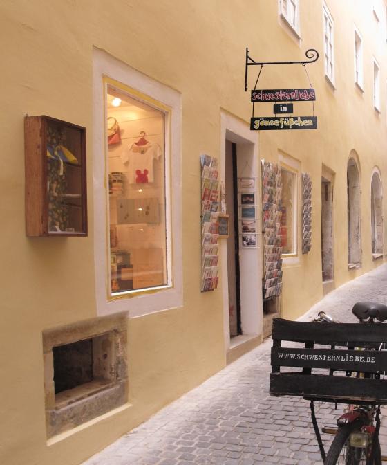 Schwesternliebe in Gänsefüßchen in der Altstadt von Regensburg in der Nähe des historischen Doms. Schon von Außen lässt sich erahnen, wie viel besondere Geschenke und Mitbringsel darauf warten, entdeckt zu werden.